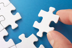 A person assembling puzzle pieces. Royalty Free Stock Photo