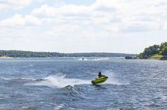 Person auf einem grünen PWC fängt Luft auf See mit anderen Booten und PWCs und Häuser und Docks auf dem Ufer im Hintergrund lizenzfreies stockbild