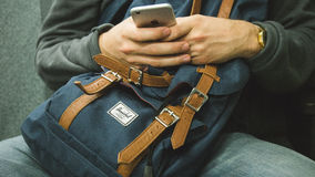 Person with backpack using mobile phone Royalty Free Stock Images