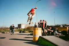 Person in Beige Pants Riding Skateboard over Yellow Metal Barrel royalty free stock images