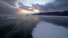 A person on bicycle in the background of the Baikal mountains. Unidentified man rides his bike, on frozen lake during winter. Magnificent landscape. The sunset stock video