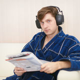 Person in big ear-phones on sofa reads newspaper Royalty Free Stock Photo
