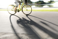 Person on bike casting shadow Royalty Free Stock Photography