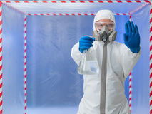 Person in biohazard suit calling a halt Stock Photo