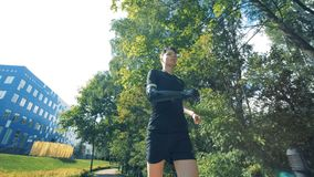 Person with bionic hand runs outdoors, close up. One man jogs with his cybernetic prosthesis