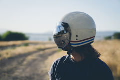 Person in Black Crew Neck Shirt Wearing White Red and Blue Helmet Standing on Field Stock Images