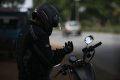 Person Black and Gray Motorcycle Jacket Wearing Black Full Face Motorcycle Helmet Standing Near on Black Motorcycle during Daytime Royalty Free Stock Images
