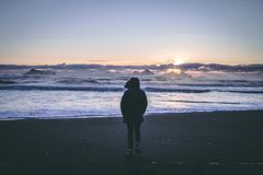 Person in Black Hoodie Near Seashore during Sunset Stock Image