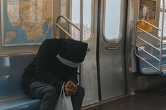 Person in Black Hoodie Sitting on Train Bench Stock Image