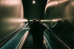 Person in Black Jacket Standing on Escalator Royalty Free Stock Photo
