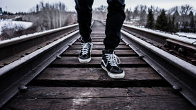 Person in Black Pants With Black Vans High Top Sneakers Standing on Railroad Tracks during Daytime Royalty Free Stock Photo