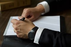 Person on Black Suit Jacket Writing on White Paper stock image