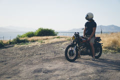 Person in Black T Shirt Sitting on Black Motorcycle Overlooking Sea during Daytime Stock Photo