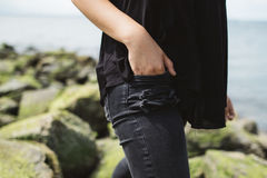 Person in Black Tops Wearing Black Denim Jeans Near Sea at Daytime Royalty Free Stock Photo