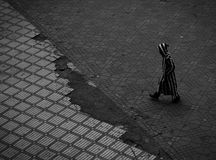 Person in Black and White Stripe Hoodie Walking on Gray Concrete Floor Stock Images