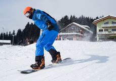 Person in Blue Coveralls Snowboarding on Snow stock photography