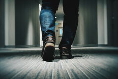 Person in Blue Denim Fitted Jeans Walking Through Hallway Royalty Free Stock Photos