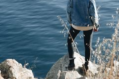 Person in Blue Denim Jacket Near in Body of Water Stock Photo