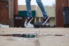 Person in Blue Denim Jeans and Brown Slip on Shoes Jumping on Body of Water Stock Photo