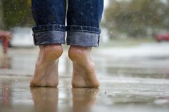 Person in Blue Denim Jeans Standing Outside the Rain Royalty Free Stock Image