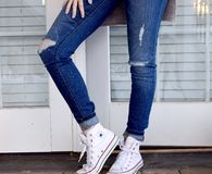 Person in Blue Denim Jeans and White Converse All Stars Royalty Free Stock Images