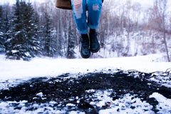 Person in Blue Distressed Denim Jeans Jumping on Snow Coated Land Near in Green Trees during Daytime Royalty Free Stock Photography