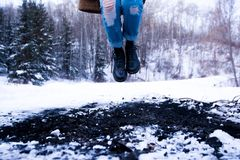 Person in Blue Distressed Denim Jeans Jumping on Snow Coated Land Near in Green Trees during Daytime Stock Photo