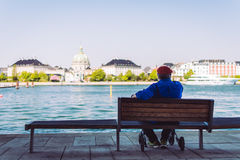 Person in Blue Dress Shirt Sitting on Brown Bench Near Body of Water Royalty Free Stock Images