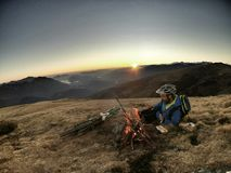 Person on Blue and Green Jacket and Green Bike in Front of Him on the Top of Mountain during Sunset Royalty Free Stock Photo