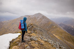 Person in Blue Hoodie Jacket Wearing Red Hiking Backpack Standing at the Top of Mountain Under White Sky during Daytime Stock Images