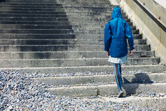 Person in blue jacket walking up stairs outside Royalty Free Stock Images
