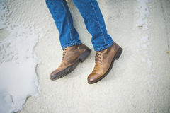 Person in Blue Jeans and Brown Leather Shoes Near White Concrete Wall Royalty Free Stock Images