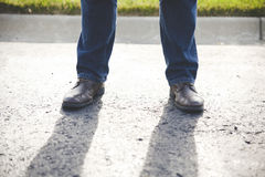 Person in Blue Jeans and Brown Oxford Shoes Standing Near Grasses Royalty Free Stock Images