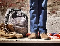 Person in Blue Jeans and Brown Suede Shoes Standing Near Camouflage Backpack Brown Hiking Boots and American Flag on Floor Royalty Free Stock Images