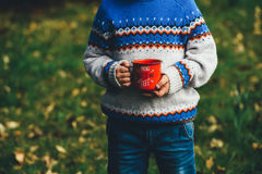 Person in Blue White and Orange Sweater Holding Red Coffee Cup on Green Grass during Daytime Royalty Free Stock Photo