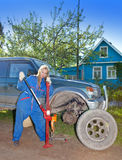 The person in blue working overalls  about the car Royalty Free Stock Images