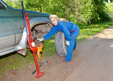 The person in blue working overalls works with a red rack jack about the car Royalty Free Stock Images