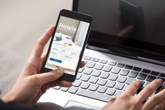 Person Booking Hotels Using Cell telefon royaltyfri foto