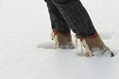 Person in boots goes on a deep snow Stock Photo