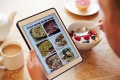 Person At Breakfast Looking At-Recept App op Digitale Tablet stock fotografie