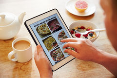 Person At Breakfast Looking At-Rezept-APP auf Digital-Tablet Lizenzfreies Stockbild