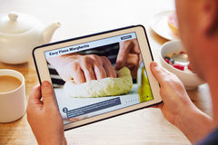Person At Breakfast Looking At-Rezept-APP auf Digital-Tablet Stockbild