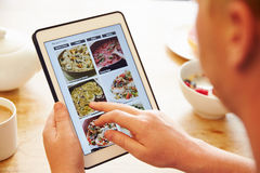 Person At Breakfast Looking At-Rezept-APP auf Digital-Tablet Lizenzfreies Stockfoto