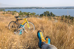 Person in bright sporty Shoes resting on Grass along Bicycle. Bicyclist in bright sporty Shoes resting on yellow autumnal Grassy Lawn along with Bike Rural View Stock Images