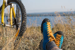 Person in bright sporty Shoes resting on Grass along Bicycle. Bicyclist in bright sporty Shoes resting on yellow autumnal Grassy Lawn along with Bicycle Rural Stock Photo