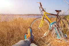 Person in bright sporty Shoes resting on Grass along Bicycle. Bicyclist in bright sporty Shoes resting on yellow autumnal Grassy Lawn along with Bicycle Rural Royalty Free Stock Photos