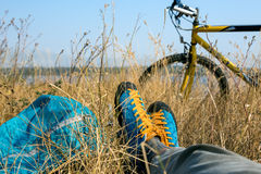 Person in bright sporty Shoes resting on Grass along Bicycle. Bicyclist in bright sporty Shoes resting on yellow autumnal Grassy Lawn along with Bicycle Rural Stock Image