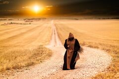 Person in Brown and Black Robe in the Middle of the Road Royalty Free Stock Images