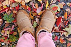 Person in Brown Sheepskin Boots and Pink Pants Standing on Leaf Covered Ground Stock Photos