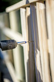 Person building a wooden fence with a drill and screw Royalty Free Stock Photo